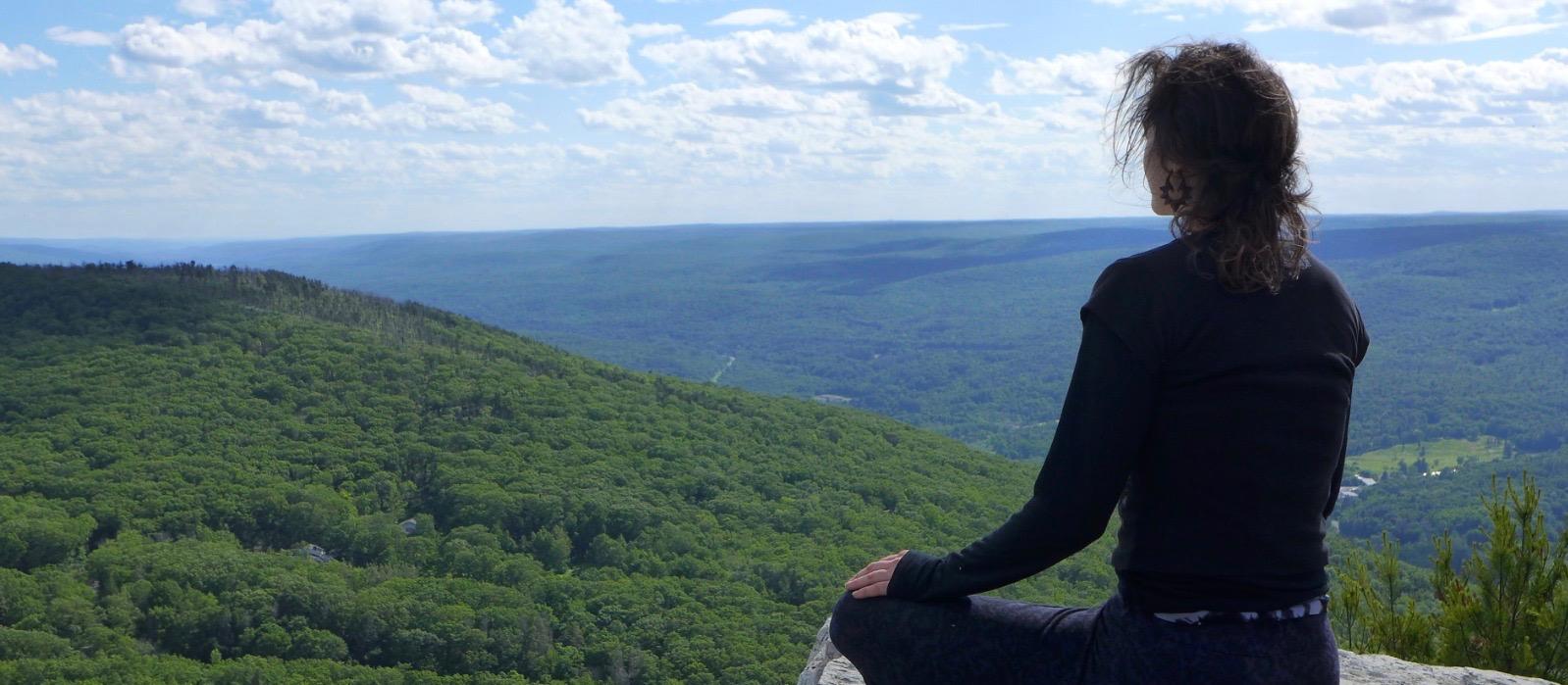 Girl meditating on a mountaintop