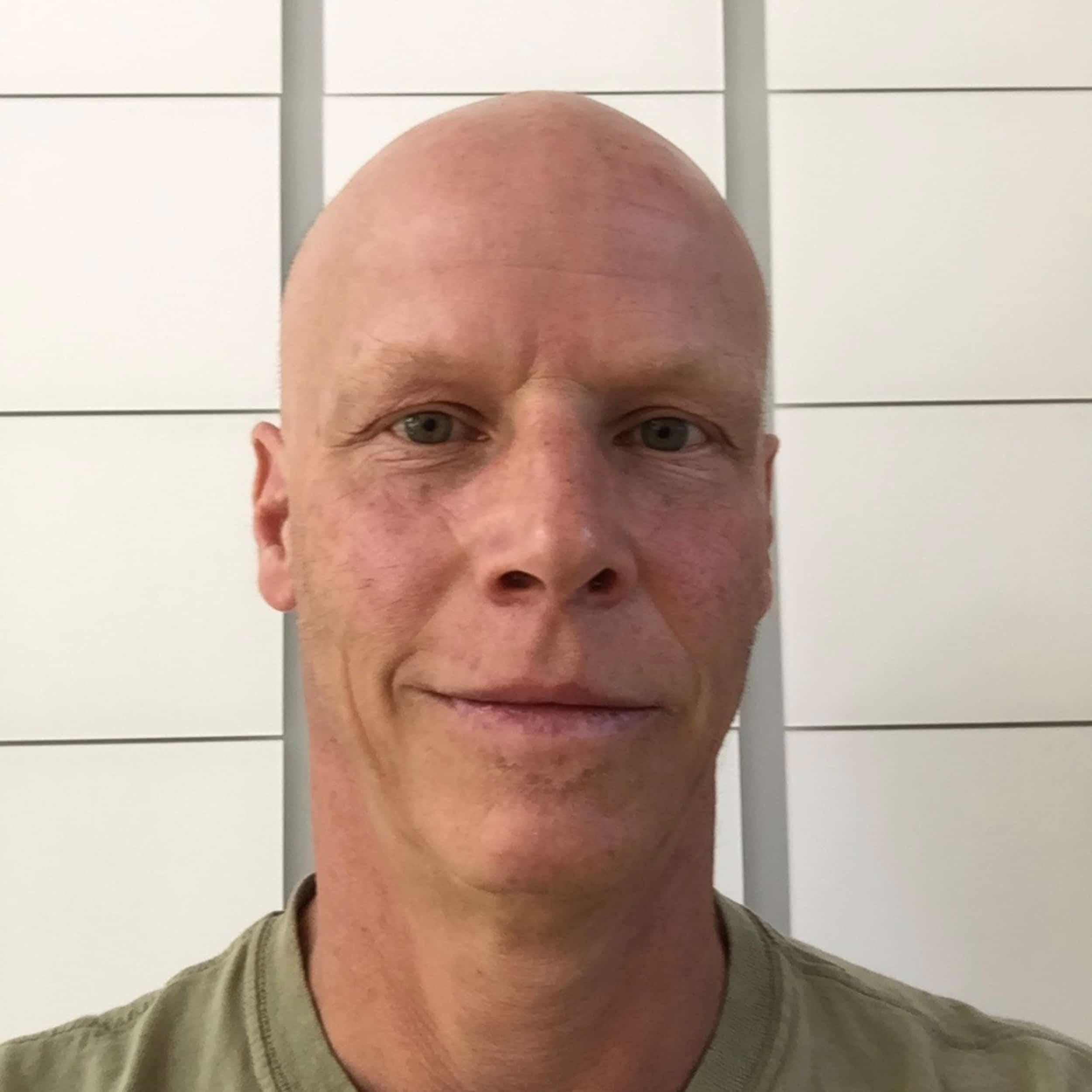 Bald man in green T shirt looking at camer